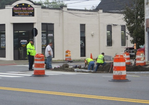 Flanked by orange and white safety barrels, men in yellow safety vests dig up the sidewalk as subervisor and police officer look on