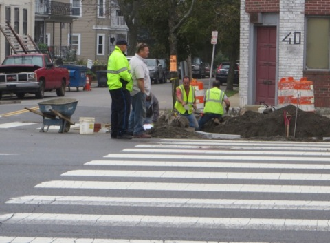 A crew working on the sidewal, with the Lafayette St. crosswalk in the foreground.